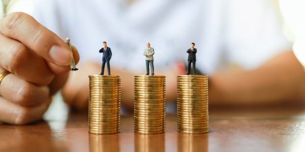 business-money-human-management-resource-concept-close-up-man-hand-holding-businessman-miniature-figure-people-putting-change-figure-top-od-stack-gold-coin-wooden-table